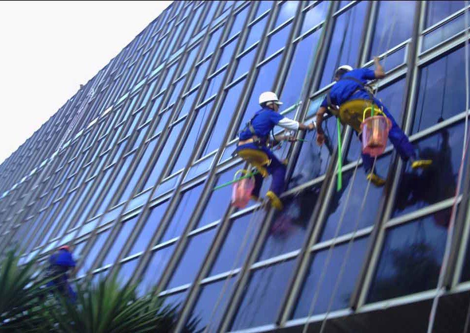 fachada predial feita de vidro. Dois restauradores estão limpando os vidros
