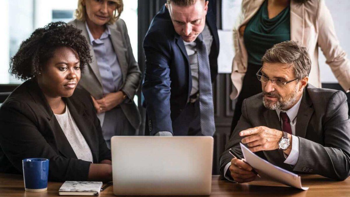 grupo de empresários, homens e mulheres, analisando um relatório no computador