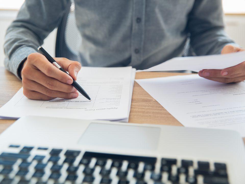 mão masculina escrevendo em papel