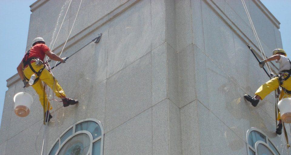 equipe de restauração suspensa em cadeiras na fachada de um prédio