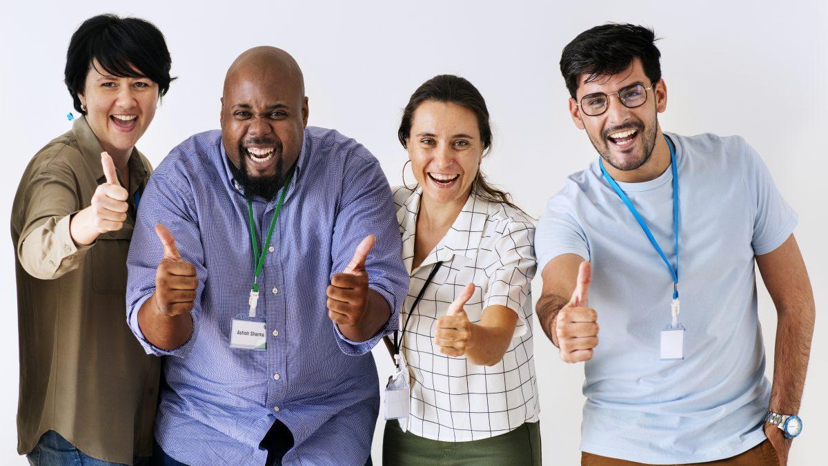 equipe de funcionários multiracial de pé com mãos estiradas para frente com o polegar levantado em sinal positivo