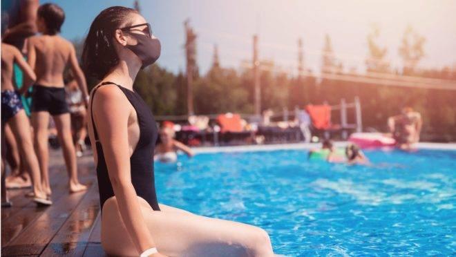 mulher usando máscara sentada na borda de na piscina de um condomínio