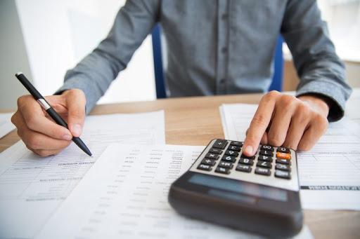 mãos masculinas usando a calculadora para calcular inadimplência no condomínio