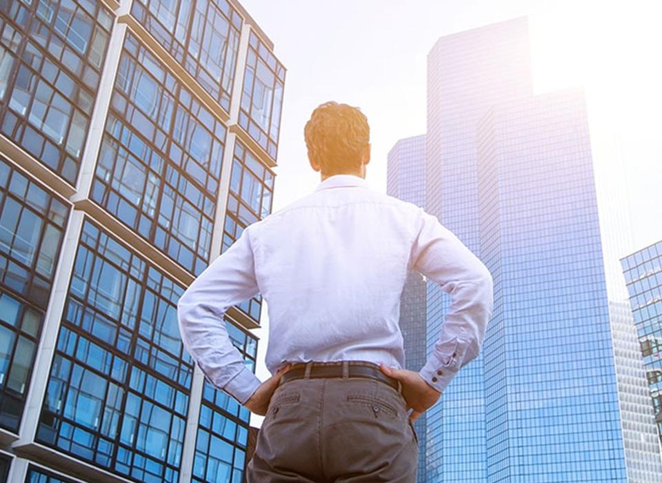 Homem de costas vestindo roupa social olhando para prédios