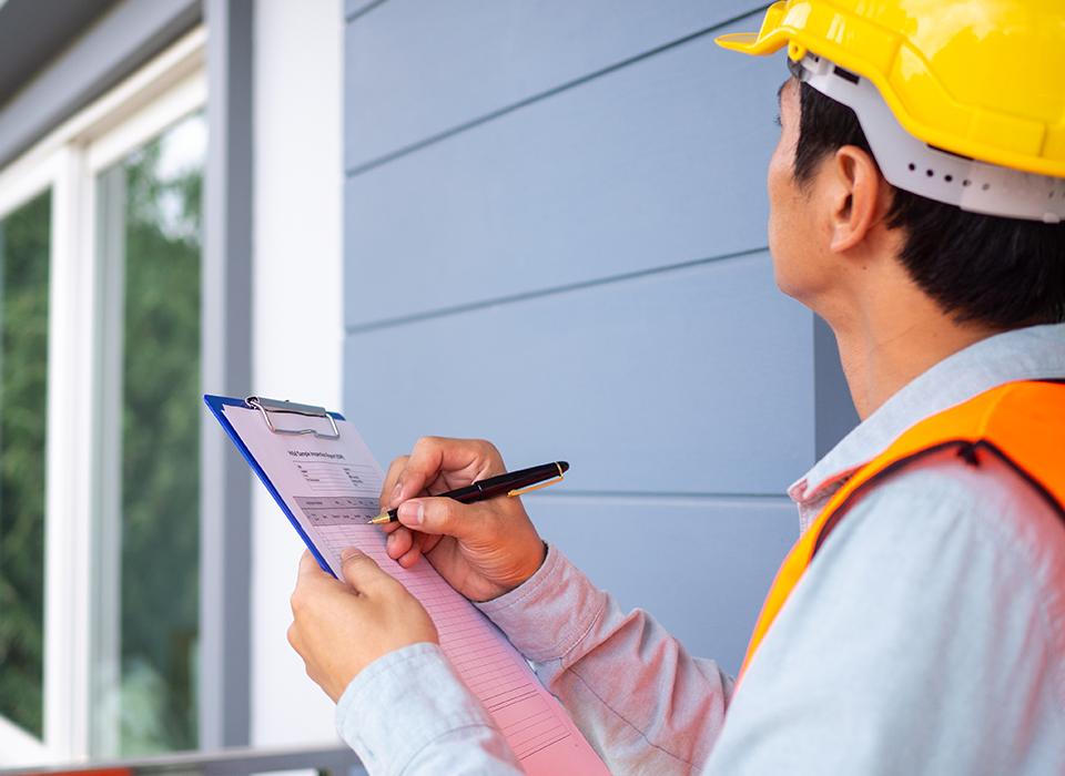 Homem com camisa social, segurando uma prancheta analisando prédios.
