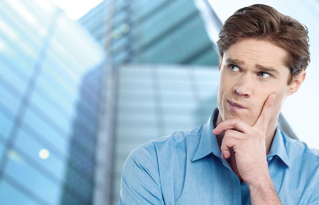 Homem branco na frente de um prédio com uma mão no rosto pensando.