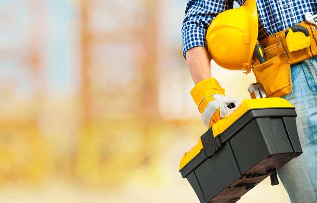 Mão de um homem segurando uma caixa de ferramentas e um capacete embaixo do braço.