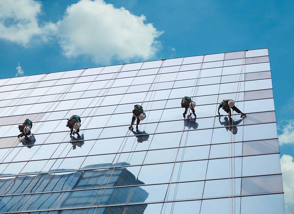 4 profissionais trabalhando na manutenção de uma fachada de prédio.
